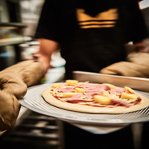 Putting a custom made pizza into the oven at Assembli salads and pizzas